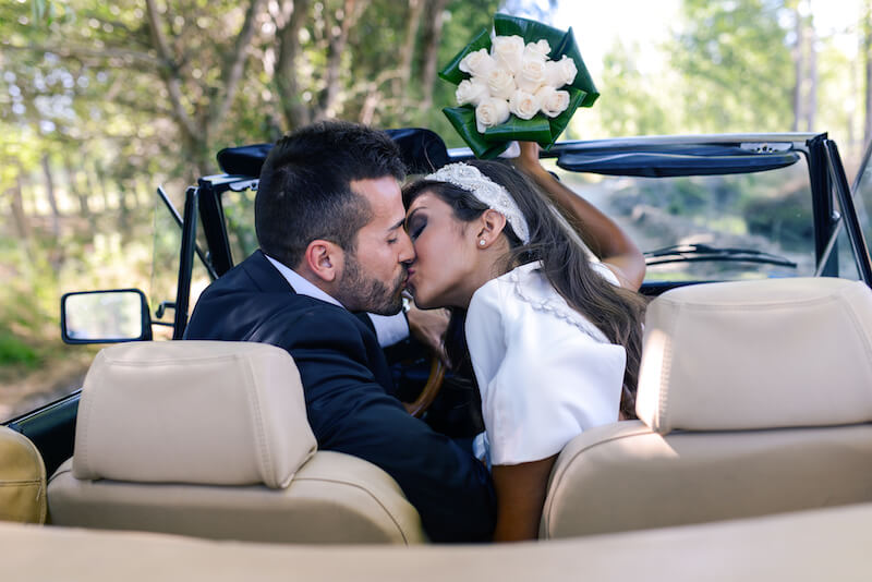 couple in wedding car kissing